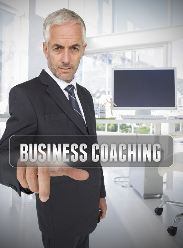 businessman-pointing-to-business-coaching-sign