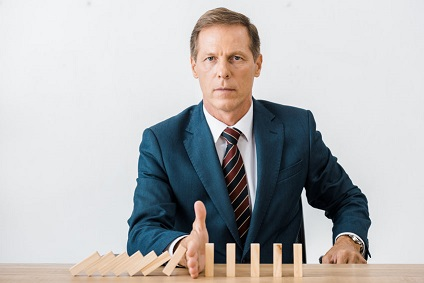 businessman-stopping-dominoes-2