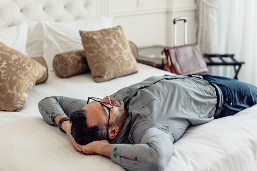 man-hotel-room-bed