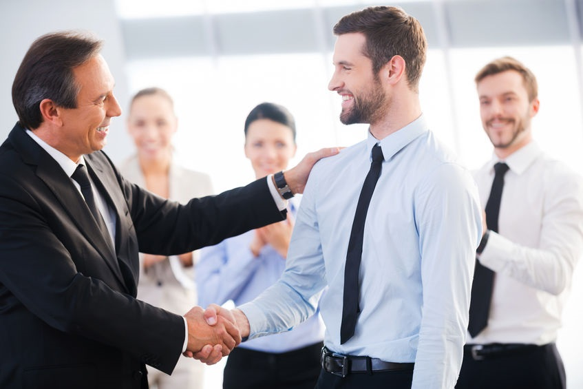 older-businessman-shaking-hands-with-younger